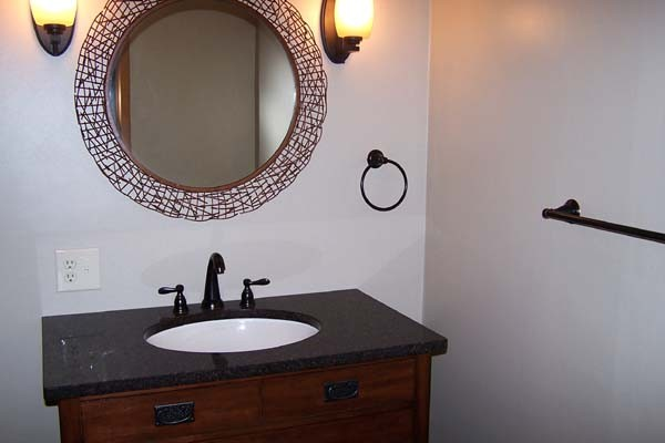 vanity with copper and round framed mirror