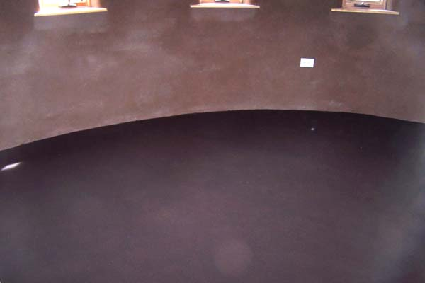 earthen plaster and curved studio wall