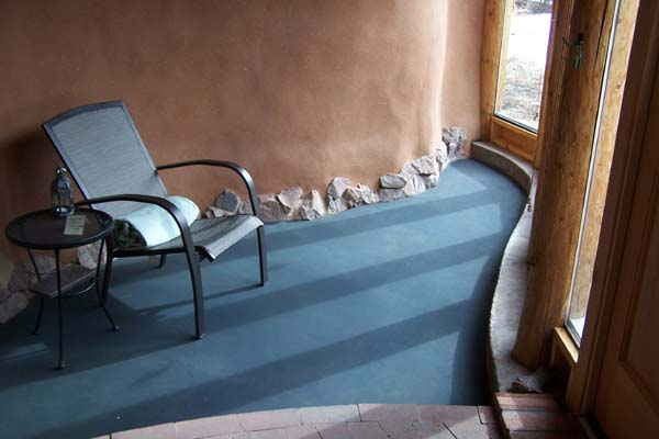 sunroom with blue alis poured adobe floor